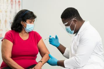 Man in a white lab cost vaccinating a woman.