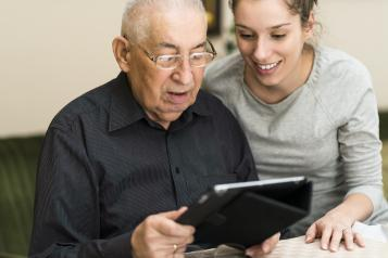 A female carer looking at an iPad with an old man.