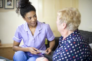 Social care worker speaking to a lady in her home