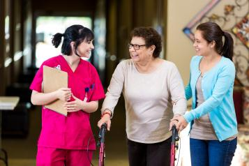 An elderly women on crutches being helped to walk by a nurse and her daughter