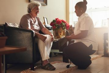 Woman in a care home speaking to worker