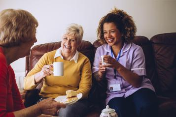 Healthcare worker and two women having a cup of tea