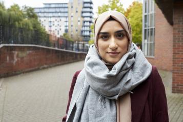 Woman wearing a headscarf standing outside