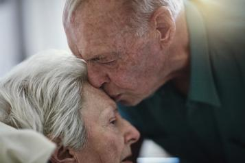 Elderly man kissing his wife on the forehead