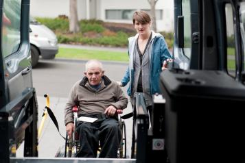 Older man in wheel chair with carer