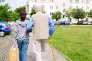 A carer supporting an elderly man with a walking stick