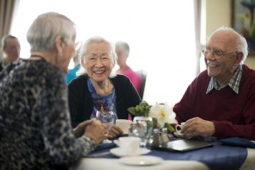 Two elderly women and a man having tea together