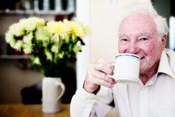 An older man drinking a cup of tea