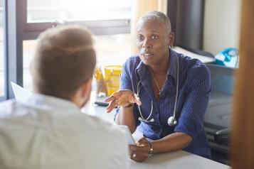 front picture of lady doctor speaking to man over a desk