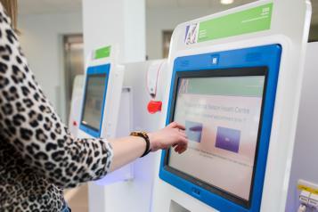 A women using a registration machine in a hospital