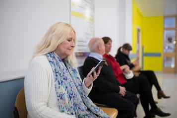A woman looking at her phone in a hospital waiting room