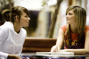 two girls speaking to each other while sitting