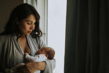 woman holding baby near a window