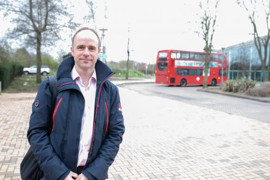 Man standing in front of a roundabout with a red bus in the background