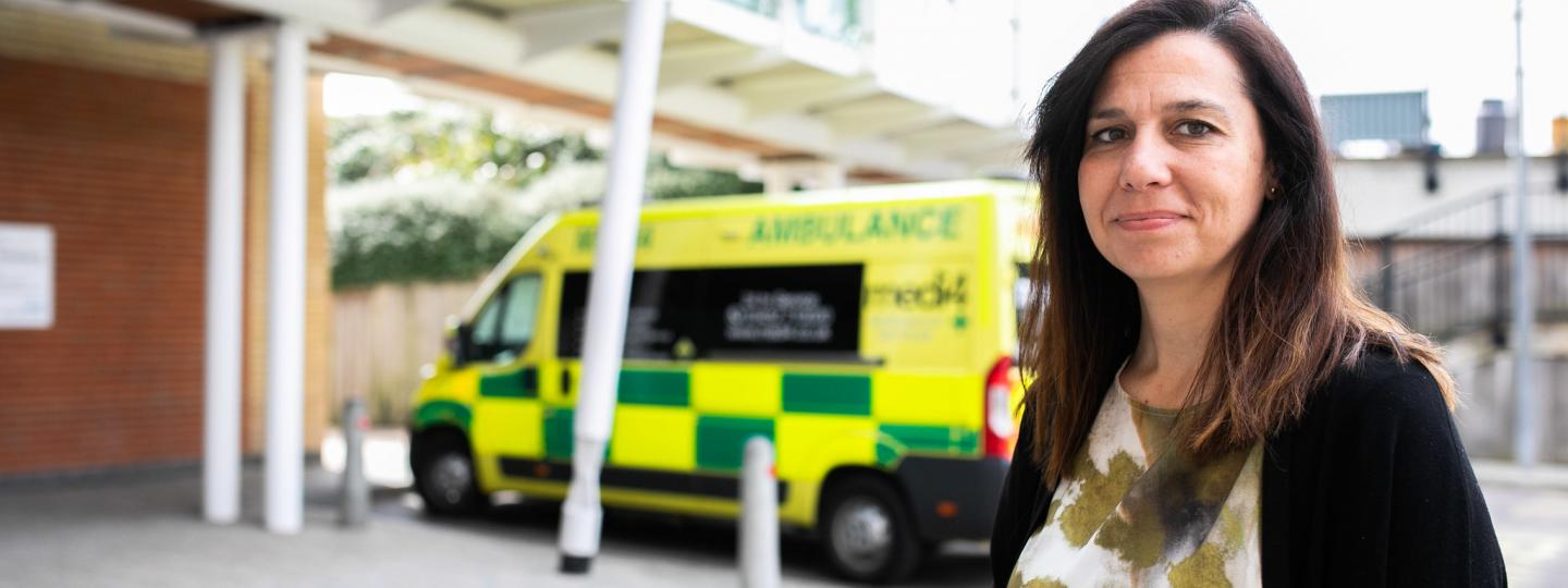Woman smiling at the camera in front or an ambulance