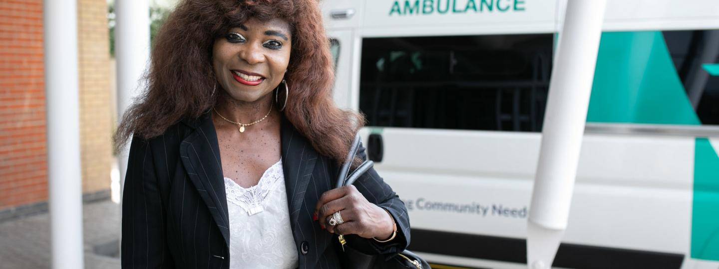 Women smiling in front of an ambulance