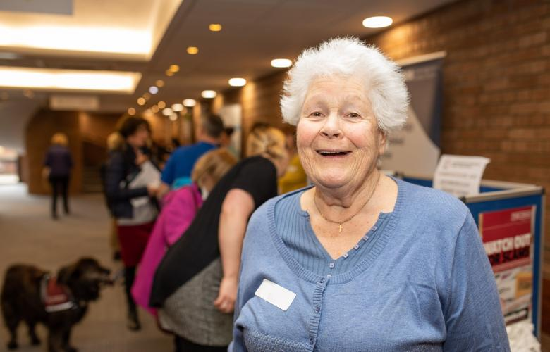 Elderly lady smiling at the camera at a Healthwatch event