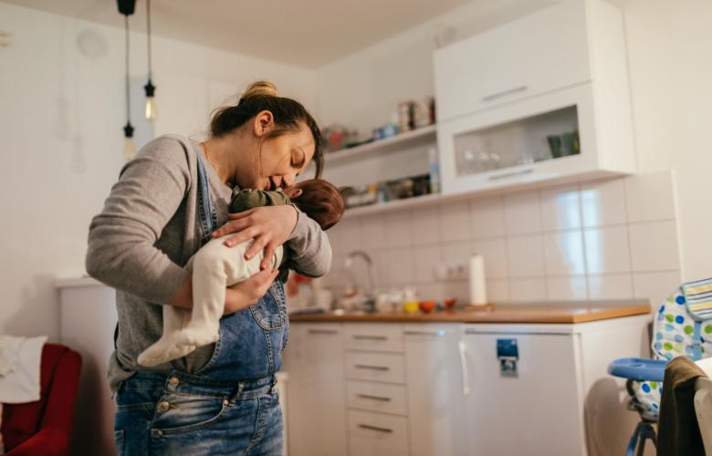Women holding a baby in her kitchen
