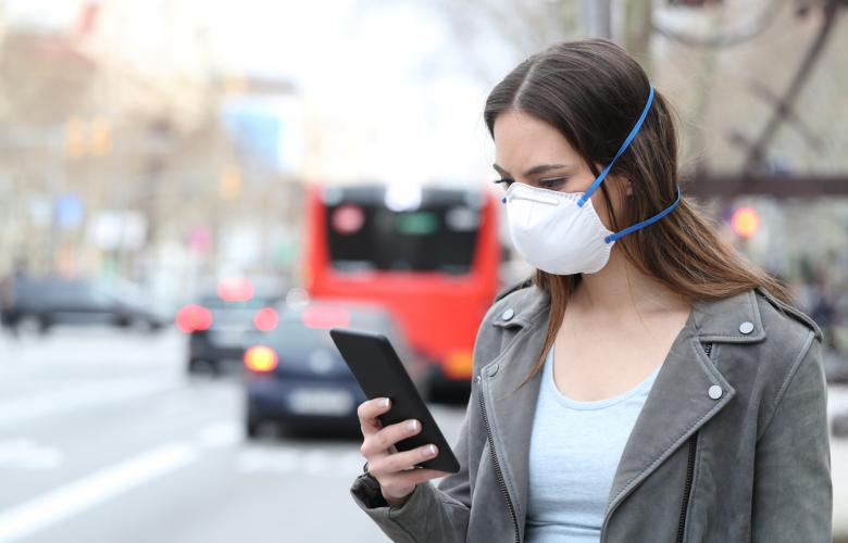 Woman with protective mask using smart phone with city traffic background