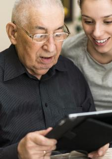 Young woman helping an elderly gentleman work a tablet