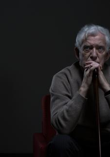 Man sitting alone in the dark with his head on his hands
